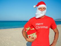 Men in santa hat. Young man in Santa hat with gift on tropical vacation Royalty Free Stock Photo