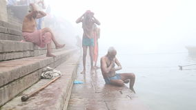 Men scrubbing their bodies on shore of foggy Ganges river in Varanasi. VARANASI, INDIA - 19 FEBRUARY 2015: Men scrubbing their bodies on shore of foggy Ganges stock video