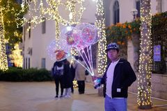 Men sell luminous balloons at night, srgb image