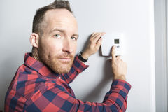 Men set the thermostat at home. A man set the thermostat at home Stock Images