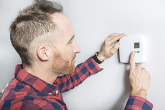 Men set the thermostat at home. A man set the thermostat at home Stock Photos