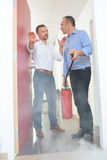 Men sets fire extinguisher at office Stock Photography
