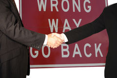 Men shake hands. In front of a warning sign Royalty Free Stock Image