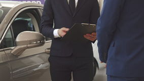Men shake hands at the dealership. Close up of two men shaking hands at the dealership. Low shot of sales manager dealing with customer at the showroom. Male stock footage