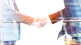 Men shaking hands closeup. Closeup of businessmen shaking hands on glass building background. Double exposure Stock Image