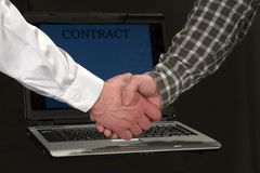 Men shaking hands in front of a laptop stock photo