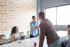 Men shaking hands on a meeting. Colleagues on a presentation on the office background. Teamwork concept. Copy space. Stock Photo