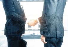 Men shaking hands. In bright office with city view and sunlight. Teamwork concept. Double exposure Stock Photography