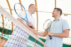 Men shaking hands over tennis court net Royalty Free Stock Photography
