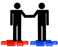 Men shaking hands on puzzle Stock Photo