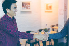 Men shaking hands. Sealing a deal! Two happy young asian businessman shaking hands while standing in coffee shop and restaurant royalty free stock photography