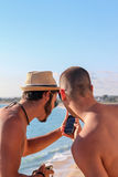 Men sharing information in smartphone. Friends sharing information in a mobile phone in a sunny day in the coast with the sea Royalty Free Stock Photo