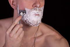 Men shaving faces. Close-up. Men shaving faces. On the black background stock photos
