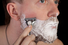 Men shaving faces. Close-up. Stock Images