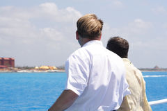 Men on a ship. Two men on teh deck of a ship looking at the shoreline Royalty Free Stock Image