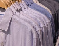 Men shirt on hanger. Official men wear in shop. Shopping mall hanger row. White striped uniform shirt. Office wear for sell and buy. Office style for man Stock Photo