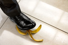 Men shoe stepping on banana peel. Top view Royalty Free Stock Photos