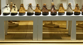 Men shoes. Modern men shoes on shelf arranged in a row Royalty Free Stock Image