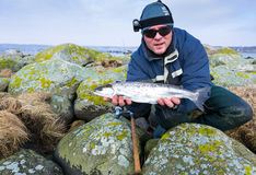 Men with silver sea trout trophy. Outdoor portrait of happy angler with silver sea trout trophy Royalty Free Stock Images