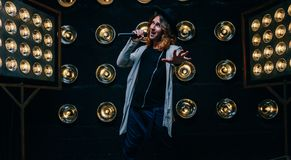 Men singer with long hair, with microphone on the stage royalty free stock image