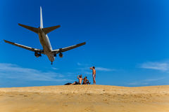 Men sit on the beach and look at them on a plane flying over on Royalty Free Stock Photo