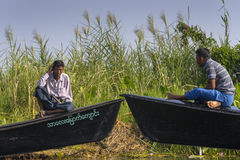 Men sit on boats Royalty Free Stock Image