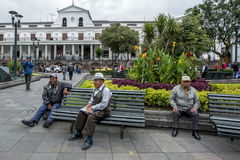 Men sit on a park bench in Independence Square in Quito in Ecuador. Stock Photos