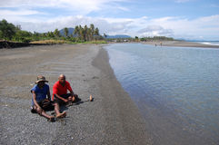 Men sit at beach river coast Stock Photo