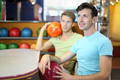 Men sit at table in bowling, hold balls Royalty Free Stock Photo