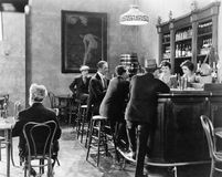Men sitting around a counter in a bar Royalty Free Stock Images