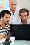 Men sitting around  laptop Royalty Free Stock Image