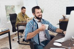 A man is sitting in a bright modern office at the computer, holding a cup of coffee or tea in his hand. Stock Photo