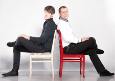 Men sitting on chairs back to back Royalty Free Stock Photo