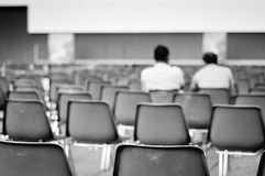Men sitting on empty chairs Royalty Free Stock Image
