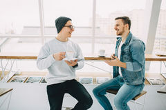 Men are sitting in front of the table near window Royalty Free Stock Photo