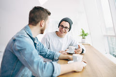 Men are sitting in front of the table near window Stock Image