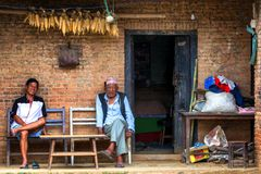 Men sitting in front of traditional house in  Nepal Stock Images