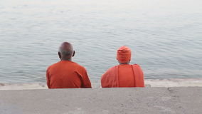 Men sitting on ghats of Ganges river, while people pass by. VARANASI, INDIA - 20 FEBRUARY 2015: Men sitting on ghats of Ganges river, while people pass by stock video footage