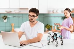 A man is sitting at the kitchen table and programming a robot. The robot is on the table. Behind the woman. A men is sitting at the kitchen table and Royalty Free Stock Photos