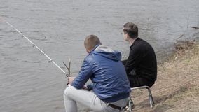 Men sitting on shore and fishing with rods in river water. Pollution ecology. Men sitting on shore and fishing with rods in river water. Young man throwing empty stock footage