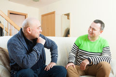 Men sitting on sofa at home and talking Stock Photo