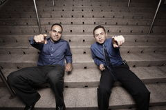 Men sitting on stairs and pointing Royalty Free Stock Images