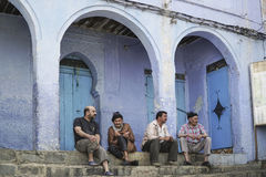 Men sitting at a street in Chefchaouen, Morocco. Men sitting at a street of the famous blue city Chefchaouen in northern Morocco Stock Photography