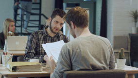 Men are sitting at table in modern offce and shaking hands, making agreement stock footage