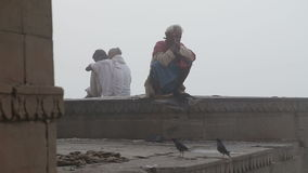 Men sitting on walls by the shore of Ganges river in Varanasi. VARANASI, INDIA - 25 FEBRUARY 2015: Men sitting on walls by the shore of Ganges river in Varanasi stock footage