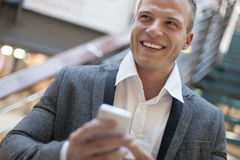 Smiling men with smartphone in business building stock photos