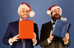 Men in smart suits and Santa hats on blue background. royalty free stock photo