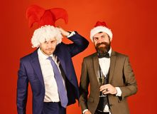 Men in smart suits, Santa and jester hats on red stock photos