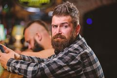 Men with smartphone relaxing at bar. Mobile dependence concept. Mobile phone always with me. Friday relaxation in bar. Hipster bearded men spend leisure at bar stock photography