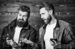 Men with smartphones surfing internet. Mobile internet. Business application. Men brutal bearded hipster in fashionable royalty free stock images